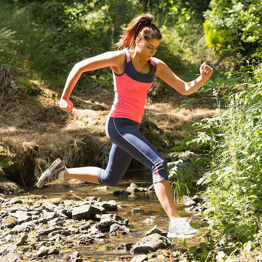 woman running in the woods for outdoor running benefits