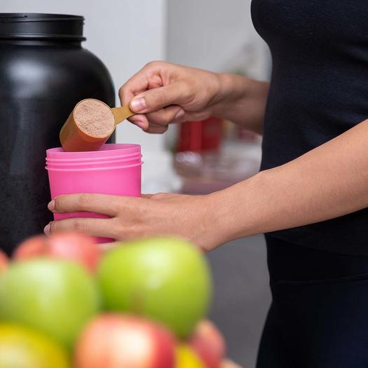 woman using best vegan protein powder for shake