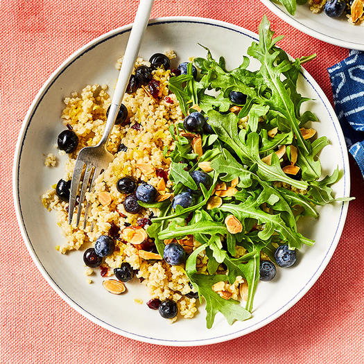 Toasted Millet Breakfast Bowl With Arugula & Blueberries on white plate