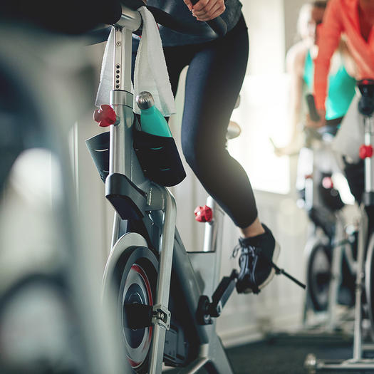 woman in spin class checking alignment on bike