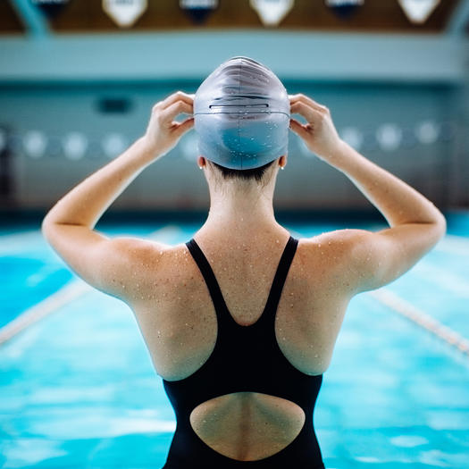 woman putting on cap for swimming workout