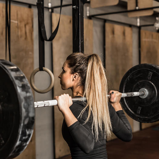 woman squatting for the benefits of lifting weights