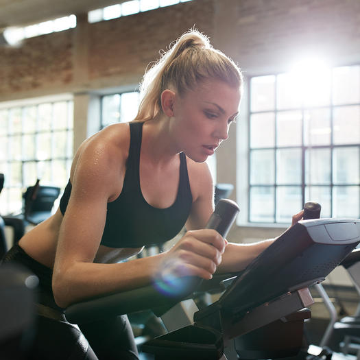 woman doing hiit on spin bike to increase metabolism