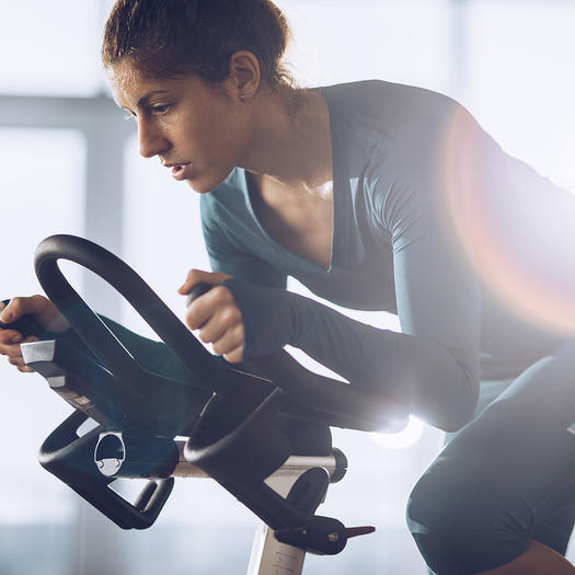 woman increasing spin resistance in cycling class