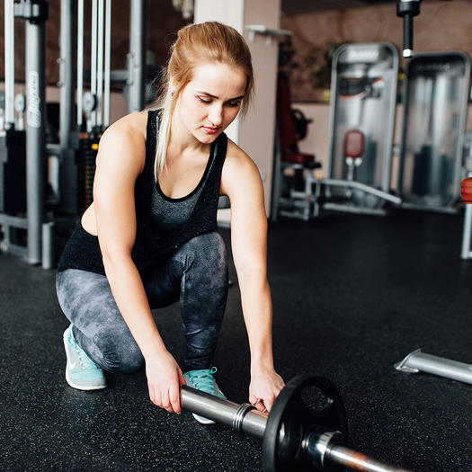 woman lifting heavy weights to build strength